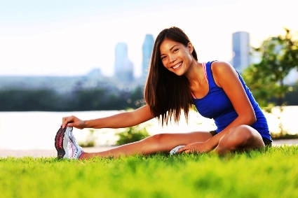 A smiling young woman is doing stretching exercises in an urban park.