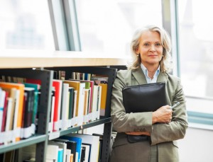Mature woman standing next to the bookshelves.