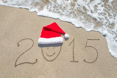 happy new year 2015 with smiley face in santa hat on sandy beach