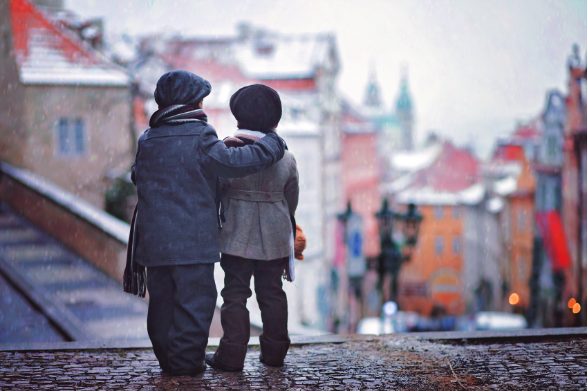Two kids, standing on a stairs, view of Prague behind them, snow
