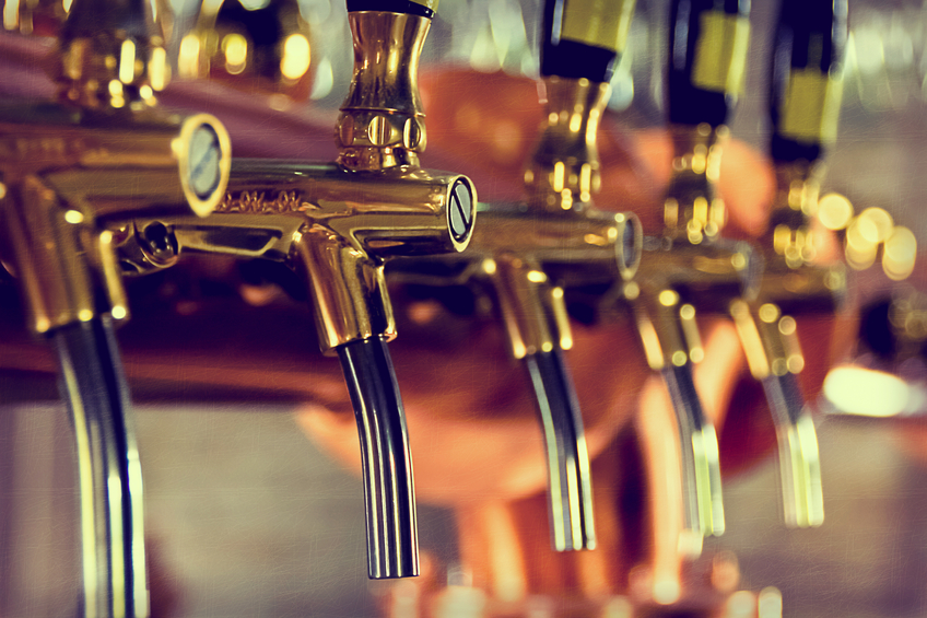 Beer taps at a bar with golden bars