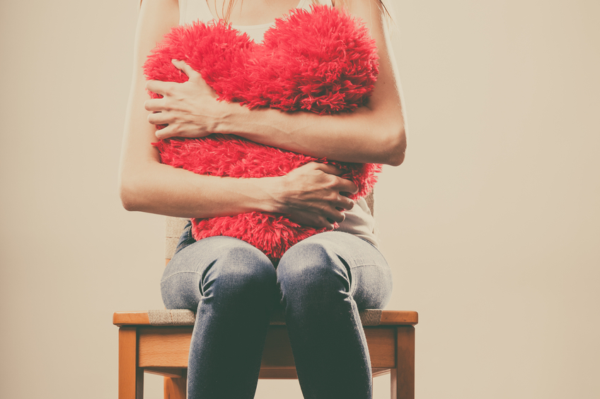 Sad unhappy woman holding red heart pillow