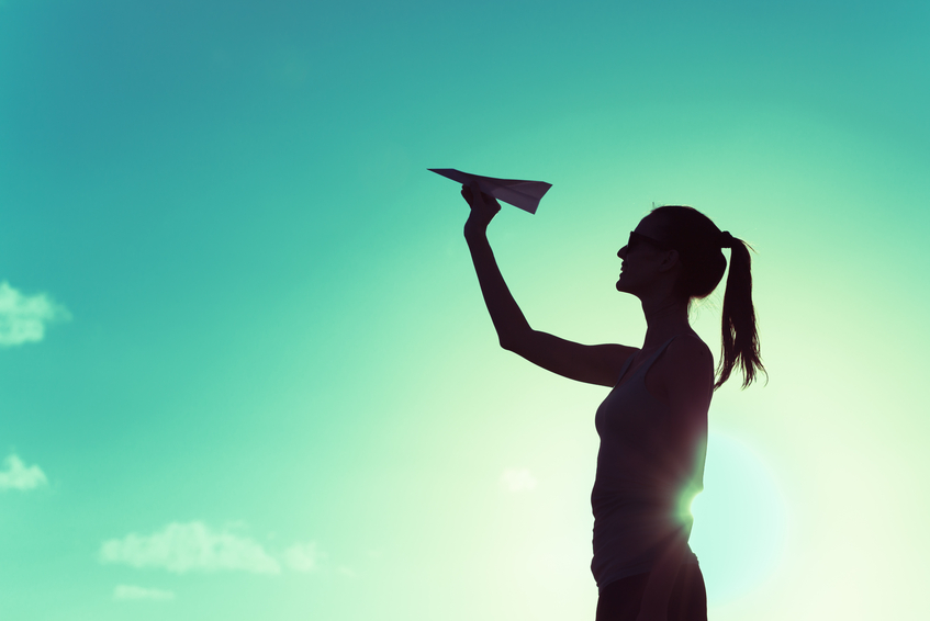 Woman throwing paper airplane