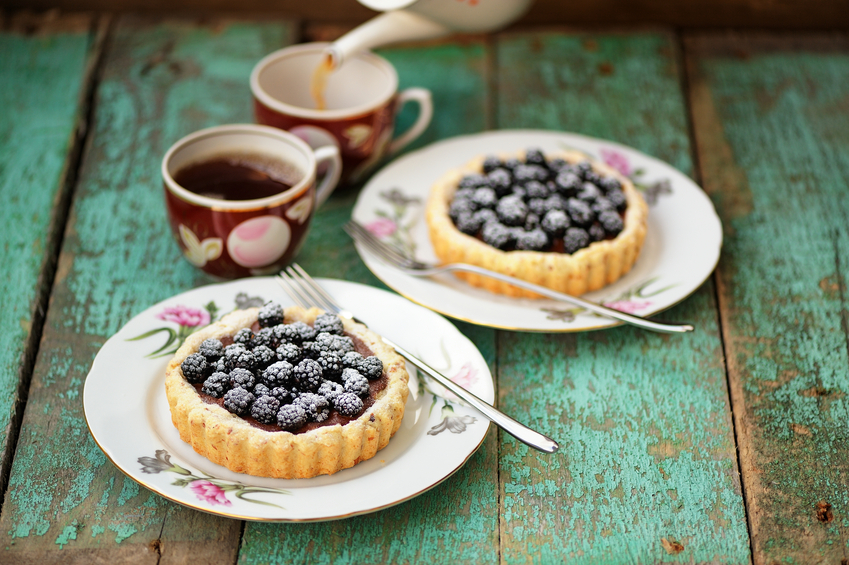 Tasty cakes with fresh wild blackberries and icing sugar