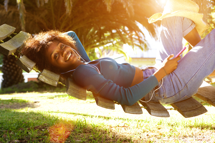 Smiling young black woman listening to music with smart phone
