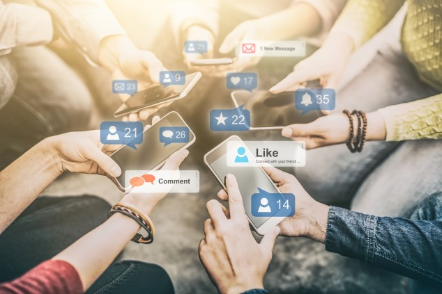 A close-up of young people sitting in a circle and holding smartphones in their hands, with social media buttons superimposed on the photo